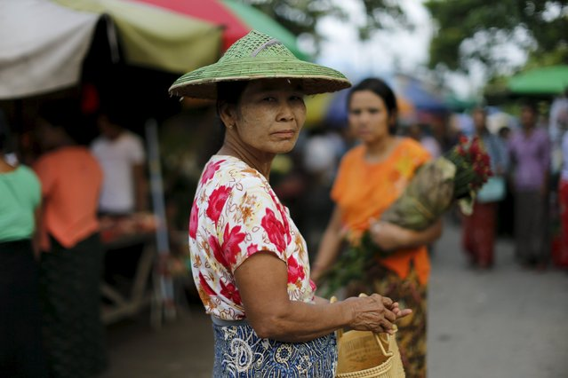 A woman reacts while walking in a market in Mandalay, Myanmar, October 7, 2015. (Photo by Jorge Silva/Reuters)