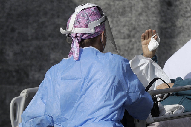 A patient waves to her relative as she is carried inside the first aid area of the Cardarelli hospital in Naples, Italy, Friday, November 13, 2020. Italian Government and health officials were analyzing data to see if the hard-strapped Campania region, which includes Naples, should be declared a red-zone. (Photo by Gregorio Borgia/AP Photo)