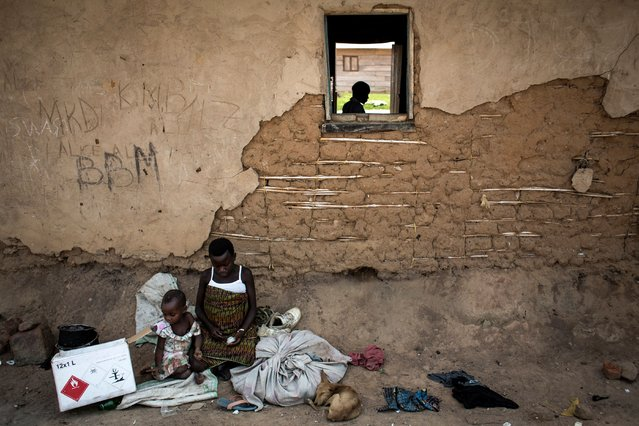 Displaced pygmies sit with their belongings outside a classroom, which serves as their shelter by night, on December 16, 2017 in Oicha, Congo. Displaced from deep in the forests, they are now struggling to adapt to more urban villages. Attacks allegedly carried out by the Ugandan Muslim Group, ADF in Eastern Democratic Republic of the Congo (DRC), have displaced thousands of Pygmies. (Photo by John Wessels/AFP Photo)