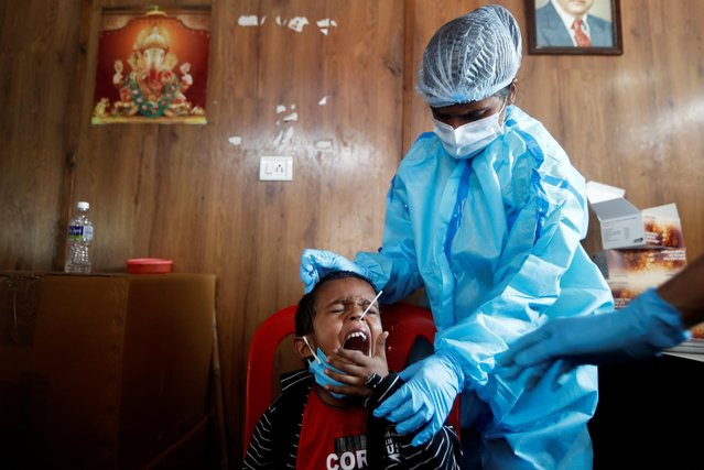 A health worker in personal protective equipment (PPE) collects a swab sample from a child during a rapid antigen testing campaign for the coronavirus disease (COVID-19), on the outskirts of Mumbai, India, November 20, 2020. (Photo by Francis Mascarenhas/Reuters)