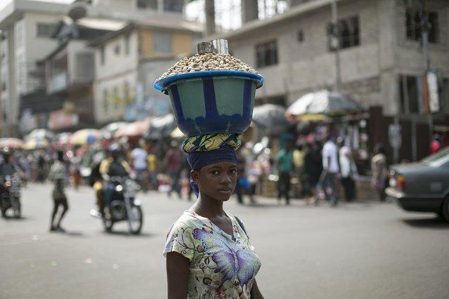 A Sierra Leonen woman carries a pot of peanuts on her head in Freetown, Sierra Leone, December 16, 2014. (Photo by Baz Ratner/Reuters)