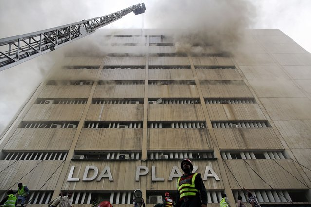 Rescue workers try to save people trapped inside a burning building in central Lahore May 9, 2013. Fire erupted on the seventh floor of the LDA Plaza in Lahore and quickly spread to higher floors leaving many people trapped inside the building. (Photo by Damir Sagolj/Reuters)