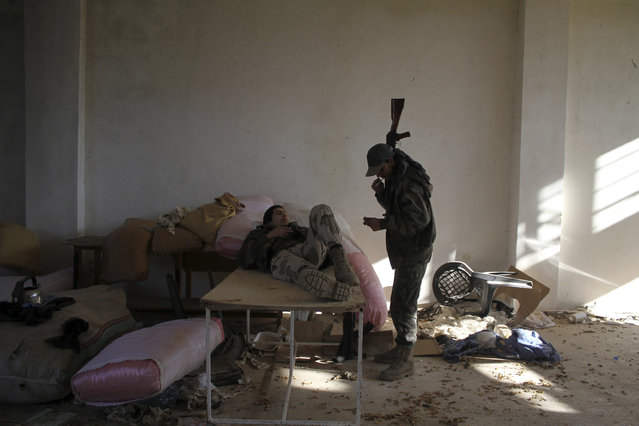 Rebel fighters rest near the frontline during their fight against forces loyal to Syria's President Bashar al-Assad in the al-Malah area, in Aleppo's countryside, December 16, 2014. (Photo by Sultan Kitaz/Reuters)