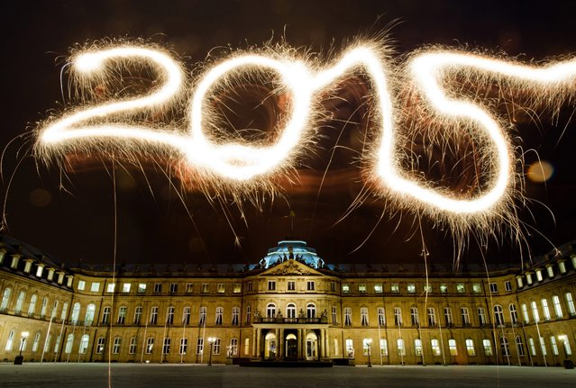 "A long exposure picture shows the number 2015 written with sparklers in the air in front of the ""Neues Schloss"" (New Palace) in Stuttgart, Germany, 29 December 2014, during preparations for New Year's Eve celebrations. (Photo by Inga Kjer/EPA)"