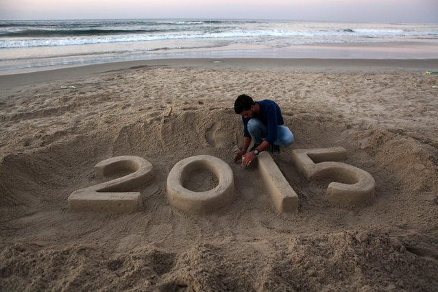 A Palestinian writes in the sand celebrating the New Year before sunset on the last day of the year in Gaza Strip, on December 31, 2014. (Photo by Majdi Fathi/NurPhoto/ZUMA Wire)