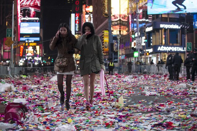 Revelers walk through confetti on the streets after New Year's Eve celebrations in Times Square, New York, January 1, 2015. (Photo by Keith Bedford/Reuters)