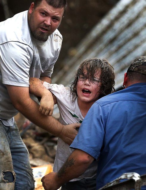 A child calls to his father after being pulled from the rubble of the Tower Plaza Elementary School. (Photo by Sue Ogrocki/Associated Press)
