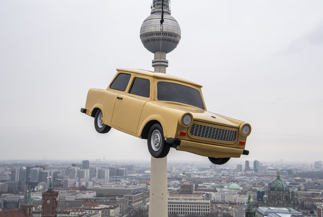 "The likeness of a Trabant, east Germany's iconic car, is suspended over a Berlin skyline with its landmark the tv tower during a publicity stunt for an amusement park, on March 3, 2020. The ""Little Big City"" amusement park will be offering virtual 3D tours of the capital in a Trabant mock-up from March 2020. (Photo by John Macdougall/AFP Photo)"