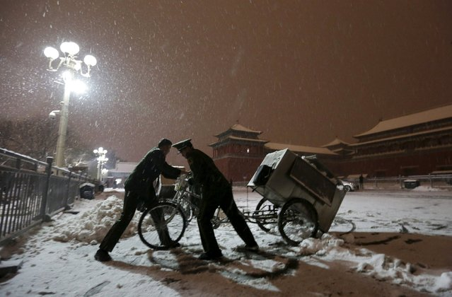 Paramilitary police officers remove snow from their camp, outside Wumen Gate of the Forbidden City as snow falls, at night in central Beijing, China, November 22, 2015. (Photo by Jason Lee/Reuters)