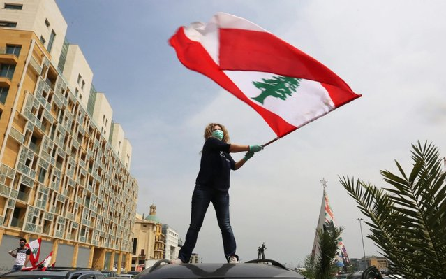 An anti-government demonstrator holds a Lebanese flag as she stands on top of her car, during a countrywide lockdown to combat the spread of the coronavirus disease (COVID-19), in Beirut, Lebanon on April 21, 2020. (Photo by Aziz Taher/Reuters)