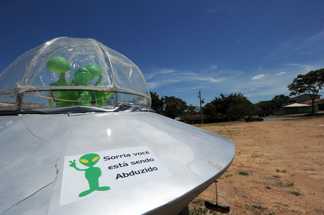 "A mock UFO with alien dolls and reading ""Smile, you are being abducted"" is seen in Alto Paraiso town, Goias State, 230 kms north of Brasilia, on December 20, 2012. Situated over a huge quartz crystal plate, Alto Paraiso attracted many Brazilians and foreigners seeking refuge from the events expected by the Mayan prophecy that predicts the end of the world or the beginning of a new era. (Photo by Evaristo Sa/AFP Photo)"
