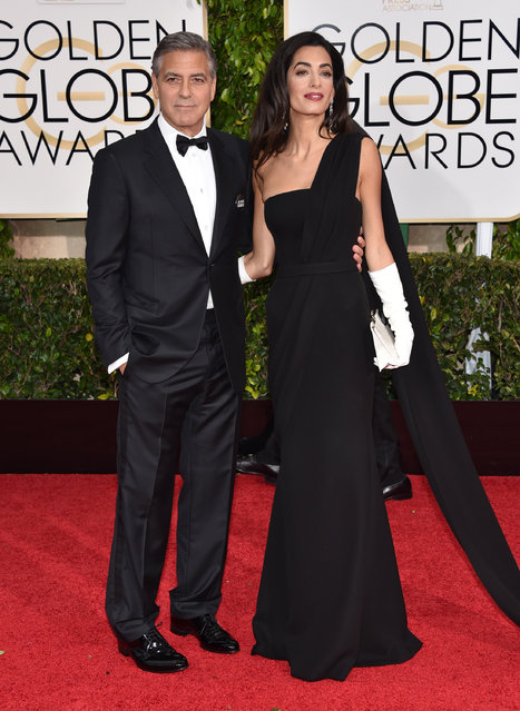 "George Clooney, left, and Amal Clooney arrive at the 72nd annual Golden Globe Awards at the Beverly Hilton Hotel on Sunday, January 11, 2015, in Beverly Hills, Calif. George is wearing a ""Je suis Charlie"" button. (Photo by John Shearer/Invision/AP Photo)"