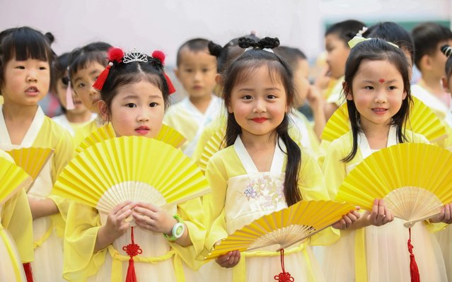 Dressed in ancient Chinese clothes, children at a local kindergarten dance and make traditional perfumed medicine bag to celebrate the upcoming Dragon Boat Festival, Ganyu district, Lianyungang city, east China's Jiangsu province, 19 June 2020. (Photo by Imaginechina via AP Images)