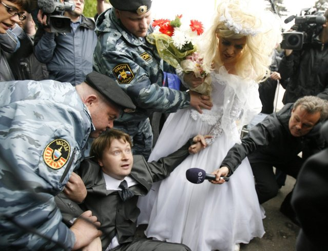 Police detain Russian gay rights leader Nikolai Alexeyev after he arrived with a man dressed in a bridal gown at an unsanctioned gay rights protest in Moscow May 16, 2009. Dozens of riot police broke up a gay rights demonstration on Saturday ahead of the Eurovision Song Contest final, grabbing protesters and throwing them into police cars and a waiting bus. (Photo by Thomas Peter/Reuters)