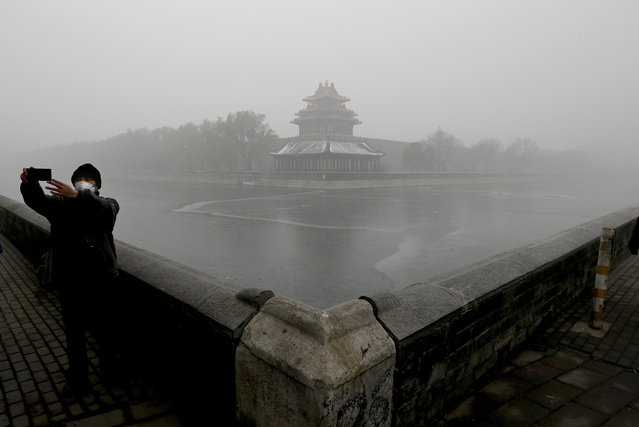 A man wearing a mask to protect himself from pollutants takes a selfie near the Turret of the Forbidden City on a heavily polluted day in Beijing, Tuesday, December 1, 2015. Schools in Beijing were ordered to keep students indoors Tuesday after record-breaking air pollution in the Chinese capital soared to up to 35 times the safety levels. (Photo by Andy Wong/AP Photo)
