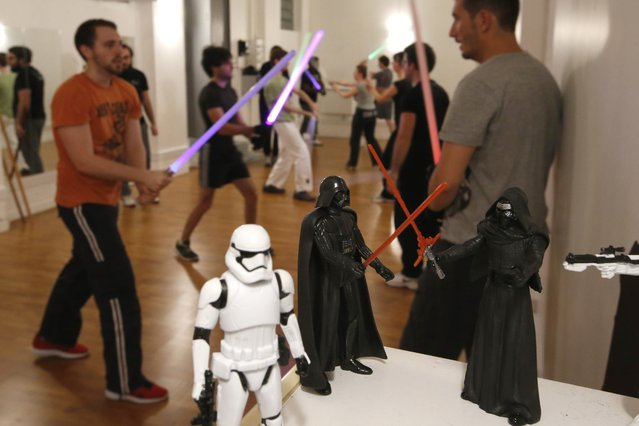 """Members of the Sport Saber League practise light saber in front of figure models from the film """"Star Wars"""" in Paris, France, November 9, 2015. (Photo by Charles Platiau/Reuters)"""