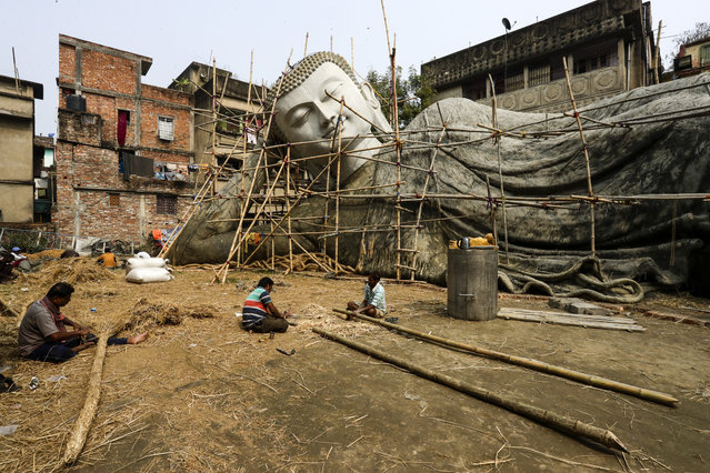 Artisans work on a clay version of a hundred-feet reclining Buddha statue in Kolkata, India, Saturday, January 30, 2021. This statue initially will be made of clay later converted into fibre glass material and will be installed at Bodhgaya, a Buddhist shrine in the Indian state of Bihar. (Photo by Bikas Das/AP Photo)