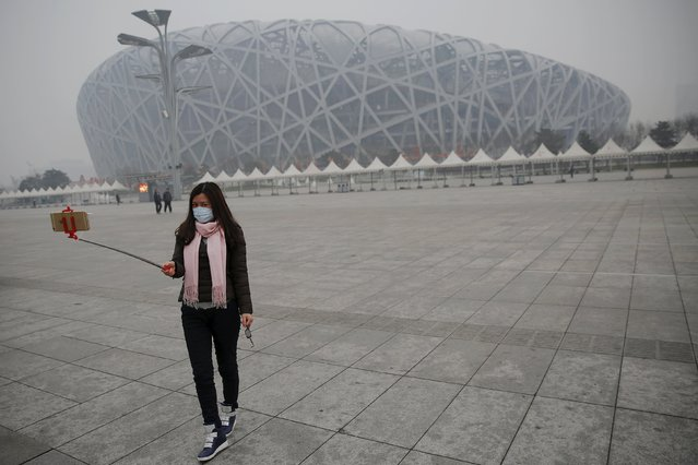 "A woman wearing a mask protecting from extreme smog takes picture in front of the National Stadium, or the Bird's Nest in Beijing December 8, 2015 as China's capital issues its first ever ""red alert"" for pollution. (Photo by Damir Sagolj/Reuters)"