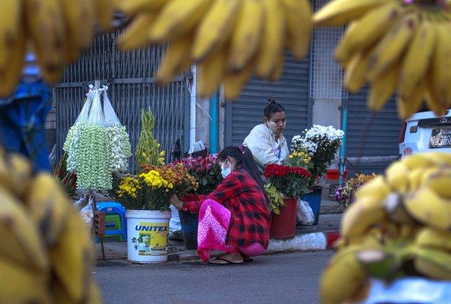 Woman arrange flowers in a street market Yangon, Myanmar, Tuesday, February 2, 2021. (Photo by Thein Zaw/AP Photo)