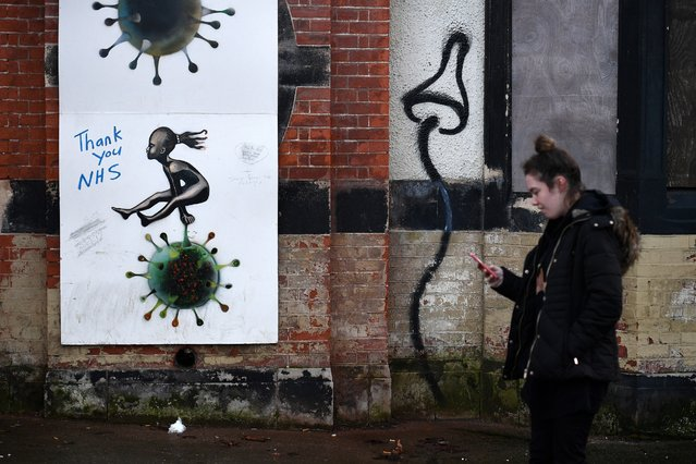 A pedestrian walks past graffiti in support of Britain's NHS (National Health Service) in Hull, in north-east England on November 30, 2020. Hull will return to the England's highest coronavirus category, Tier 3, when England exits its second lockdown an re-enters a tiered system of toughened regional restrictions on December 2. Britain has been Europe's worst-hit country during the pandemic, recording more than 57,000 deaths from some 1.6 million cases. (Photo by Oli Scarff/AFP Photo)