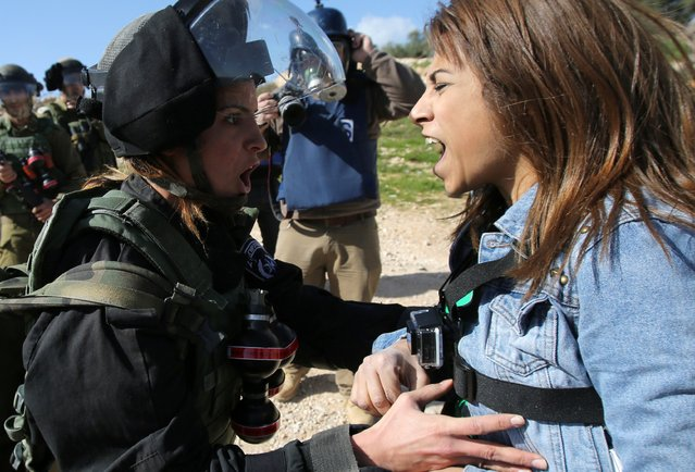 "A Palestinian activist, Lema Nazeeh, argues with an Israeli soldier during clashes between security forces and Palestinians from the West Bank village of Bilin on January 30, 2015 in Bilin, west of Ramallah, following a march to protest against Israeli settlements. Israel published tenders to build 450 new settler homes in the occupied West Bank, a watchdog said, in a plan denounced by the Palestinians as a ""war crime"". (Photo by Abbas Momani/AFP Photo)"