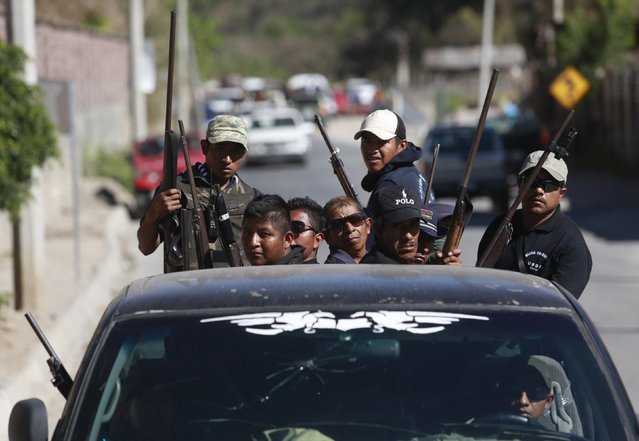 Members of the Community Police of the FUSDEG (United Front for the Security and Development of the State of Guerrero) travel at the back of a lorry after a shootout with a group that villagers suspected of belonging to a local gang, in the village of Petaquillas, on the outskirts of Chilpancingo, in the Mexican state of Guerrero, February 1, 2015. (Photo by Jorge Dan Lopez/Reuters)