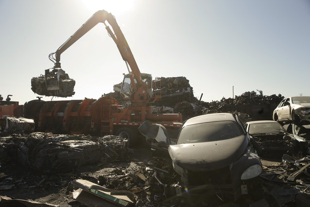 In this Wednesday, November 11, 2015 photo, a crane moves junk cars crushed into a cube at Aadlen Brothers Auto Wrecking, also known as U Pick Parts, in the Sun Valley section of Los Angeles. (Photo by Jae C. Hong/AP Photo)