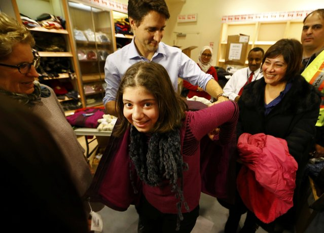 Canada's Prime Minister Justin Trudeau helps a young Syrian refugee try on a winter coat after she arrived with her family from Beirut at the Toronto Pearson International Airport in Mississauga, Ontario, Canada December 11, 2015. After months of promises and weeks of preparation, the first Canadian government planeload of Syrian refugees landed in Toronto on Thursday, aboard a military aircraft met by Prime Minister Justin Trudeau. (Photo by Mark Blinch/Reuters)