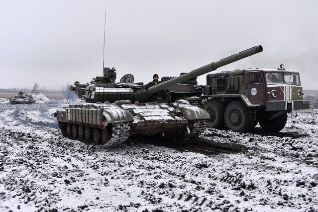 Ukrainian servicemen ride in a tank past a towing truck outside Debaltseve, eastern Ukraine February 10, 2015. (Photo by Alexei Chernyshev/Reuters)