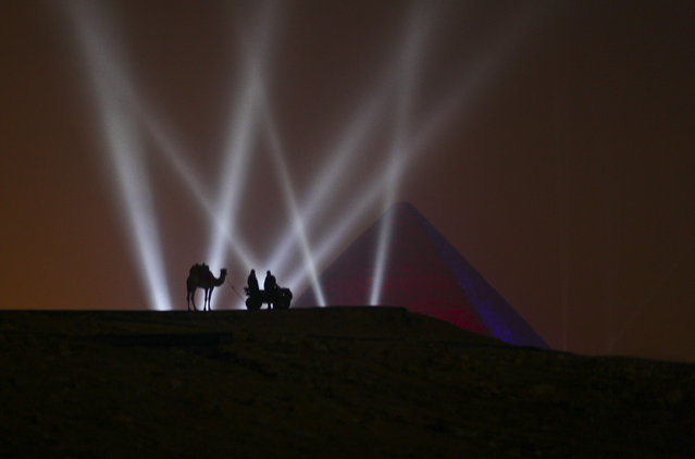 Two Egyptian men and a camel stand on a hill overlooking one of the Giza Pyramids during a New Year's Eve fireworks display near Cairo, Egypt at midnight on Friday, January 1, 2016. (Photo by Maya Alleruzzo/AP Photo)