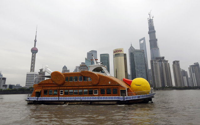 """A ferry in the shape of a duck is seen on the Huangpu River in front of the Pudong Financial area in Shanghai, August 26, 2013. The ferry was designed and remade by several Chinese artists, who claimed they were paying tribute to Dutch conceptual artist Florentijn Hofman's creation """"Rubber Duck"""". The ferry will be on exhibition for a month as part of the Bund Art Project of 2013, local media reported. (Photo by Aly Song/Reuters)"""