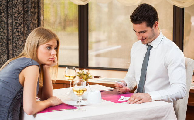 Woman is getting bored on date while her boyfriend is typing SMS. (Photo by Mladen Mitrinovi/Getty Images/iStockphoto)