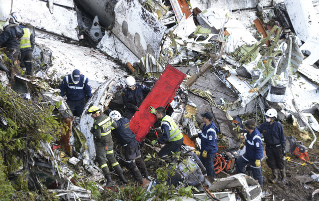 Rescue workers comb through the wreckage site of an airplane crash, in La Union, a mountainous area near Medellin, Colombia, Tuesday, November 29, 2016. The chartered plane was carrying a Brazilian soccer team to the biggest match of its history when it crashed into a Colombian hillside and broke into pieces, killing 75 people and leaving six survivors, Colombian officials said Tuesday. (Photo by Fernando Vergara/AP Photo)