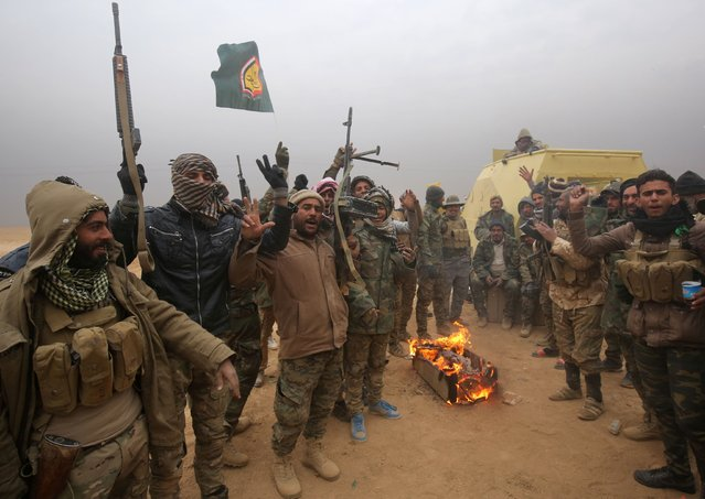 Iraqi Shiite fighters from the Hashed al- Shaabi (Popular Mobilisation) paramilitaries gesture to the camera as they warm up around a fire near the village of Tal Faris, south of Tal Afar, on November 30, 2016, during a broad offencive by Iraq forces to retake the city Mosul from jihadists of the Islamic State group. (Photo by Ahmad Al- Rubaye/AFP Photo)