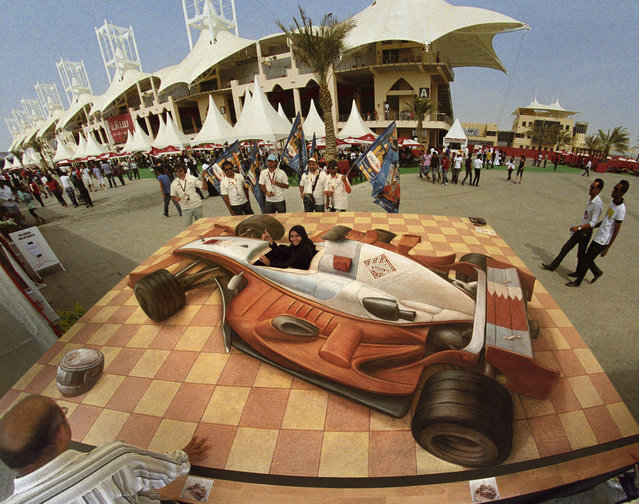 The Woman Driver is displayed in March 2008 in Bahrain. This illusion of an F1 racecar has a hole cut out for the public to sit in and pose for pictures. A stunning new book takes readers into the world of master street artist Kurt Wenner. Bringing pavements around the world to life, Kurt, 52, uses a clever technique in his street drawings that make them look perfectly 3D. When viewed from the correct angle, street-goers standing on top of them look like they are floating in thin air and solid concrete appear as gaping chasms in a colourful illusion. Pioneer Kurt, from the USA, has been perfecting his unique art since 1982 when he began sketching on the streets of Rome. His wizardry with the world's streets has now been brought together in new book Asphalt Renaissance, by Sterling Innovation publishers, available now through Amazon. (Photo by Kurt Wenner/Barcroft Media/Getty Images)