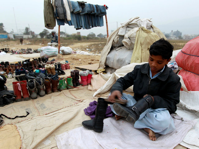 A boy polishes shoes for the winter at a used shoe market in Islamabad, Pakistan November 22, 2016. (Photo by Caren Firouz/Reuters)