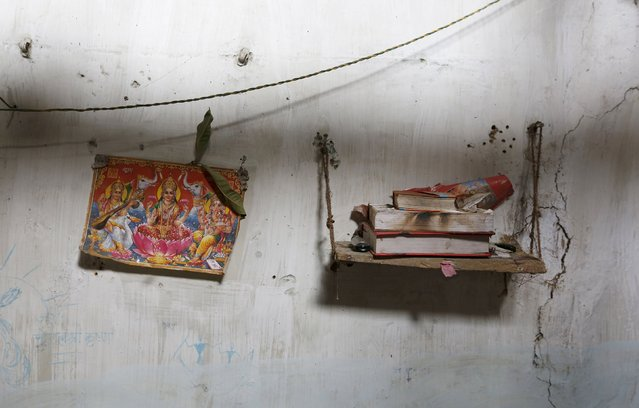 "A picture of a Hindu deity and the holy book ""Ramayana"" are seen inside the house of a Ramnami Samaj follower in the village of Chandlidi, in the eastern state of Chhattisgarh, India, November 17, 2015. (Photo by Adnan Abidi/Reuters)"