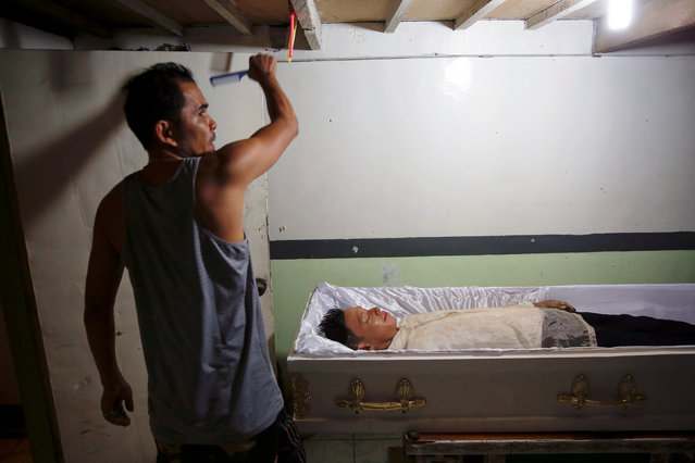A funeral parlour worker reaches for a comb to fix the hair of Florjohn Cruz after his autopsy at Eusebio Funeral Service in Manila, Philippines October 28, 2016. (Photo by Damir Sagolj/Reuters)