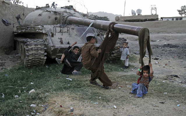 Afghan children play on the remains of a old Soviet tank in the city of Kandahar south of Kabul, Afghanistan, Tuesday, October 1, 2013. (Photo by Allauddin Khan/AP Photo)