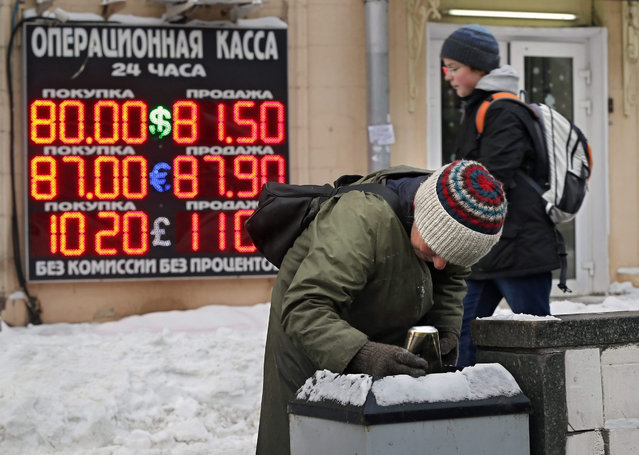 A woman searches for food in a trash bin in front of a board listing foreign currency rates against the Russian ruble in central Moscow, Russia, 20 January 2016. Russia's ruble currency fell to a record low versus the US dollar on 20 January as prices for the country's main export, oil, continued to tumble. The ruble slipped past the mark of 80.1 per US dollar in intraday trading, surpassing the previous record set in December 2014, according to a post on the Moscow Exchange bourse's website. Falling oil prices have the potential to jeopardize Russia's stability by severely weakening its economy. (Photo by Yuri Kochetkov/EPA)