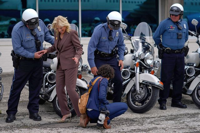 US First lady Jill Biden is helped after getting the heal of her shoe stuck in the pavement while being photographed with members of her motorcade escort before boarding her plane at Charles B. Wheeler Downtown Airport in Kansas City, Missouri on May 27, 2021, en route to Washington, DC. (Photo by Carolyn Kaster/Pool via AFP Photo)