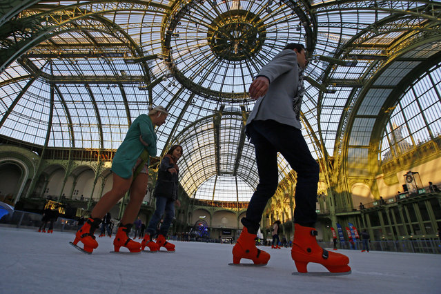 People ice skate at the Grand Palais in Paris, Thursday, December 15, 2016. The Grand Palais skating rink opened to the public on Sunday and is the largest temporary ice rink created in France during holiday (Photo by Francois Mori/AP Photo)