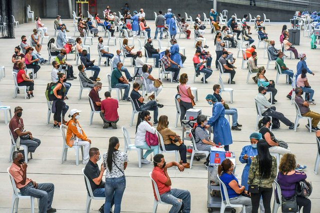 People over 50 years of age are inoculated against COVID-19 at a vaccination centre mounted at a volleyball arena in Medellin, Colombia, on June 1, 2021, amid the ongoing novel coronavirus pandemic. (Photo by Joaquin Sarmiento/AFP Photo)