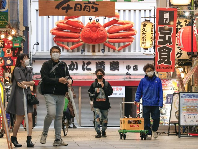 People wearing a face mask walk through downtown Osaka, western Japan, Friday, May 7, 2021. Trains packed with commuters returning to work after a weeklong national holiday. Frustrated young people drinking in the streets because bars are closed. Protests planned over a possible visit by the Olympics chief. (Photo by Yukie Nishizawa/Kyodo News via AP Photo)