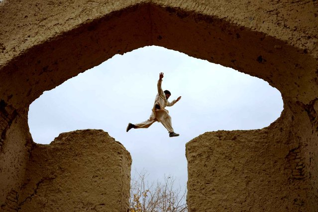 An Afghan boy plays in the ruins of a house that at one point belonged to the 13th-century Persian poet, Islamic scholar and Sufi mystic Jalal ad-Din Muhammad Rumi on the outskirts of Mazar-i-Sharif on November 25, 2015. (Photo by Farshad Usyan/AFP Photo)