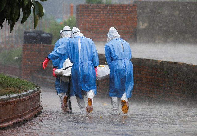 Members of Nepal Army wearing personal protective equipment (PPE) carry the body of a person, who died from the coronavirus disease (COVID-19), in the rain at the crematorium, in Kathmandu, Nepal on May 11, 2021. (Photo by Navesh Chitrakar/Reuters)