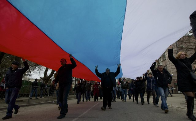 In this Saturday, March 1, 2014 file photo local residents carry a Russian flag and shout slogans rallying over the streets in Simferopol, Crimea. (Photo by Ivan Sekretarev/AP Photo)