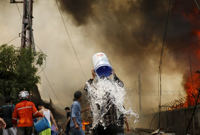 A man douses himself with water during a fire in a slum area next to railway tracks in Kampung Bandan, North Jakarta, Indonesia January 26, 2016. (Photo by Reuters/Beawiharta)