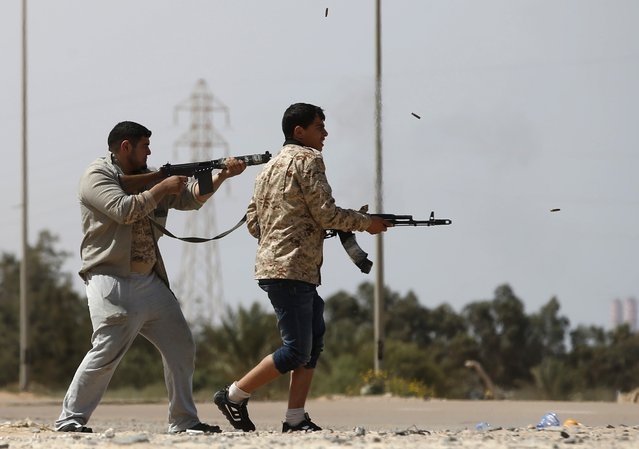 Fighters from Misrata fire weapons at Islamic State militants near Sirte March 15, 2015. Militants loyal to Islamic State, the group which has seized much of Iraq and Syria, have established a larger presence in central Libya in recent weeks. Islamic State, which analysts say is splintered into smaller factions in Libya, has sought to exploit turmoil in the major oil producer where two rival governments and their respective allies fight for power. (Photo by Goran Tomasevic/Reuters)