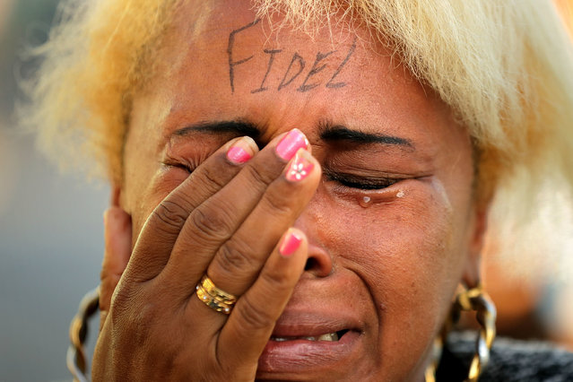 """A woman with """"Fidel"""" written on her forehand wails after joining thousands of other Cubans who lined the famous Malecon seaside boulevard to pay their respects as to former Cuban President Fidel Castro's remains began their journey across the country November 30, 2016 in Havana, Cuba. The revolutionary leader who brought commmunism to his island nation in 1959, Fidel Castro died November 25 at the age 90 years old. (Photo by Chip Somodevilla/Getty Images)"""